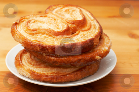 Palmier pastries on white saucer stock photo, Palmier pastries on white saucer, shot on wooden board background by Elena Weber (nee Talberg)
