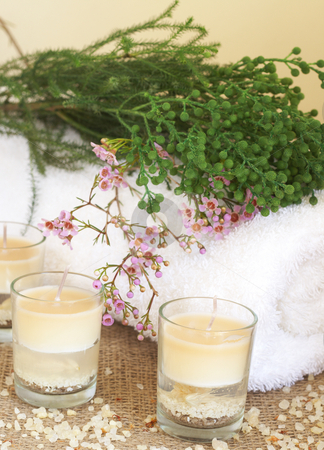 Relaxing spa scene stock photo, Relaxing spa scene with a white rolled up towel, pink and green flowers, beautiful handmade candles and bath salts by Elena Weber (nee Talberg)