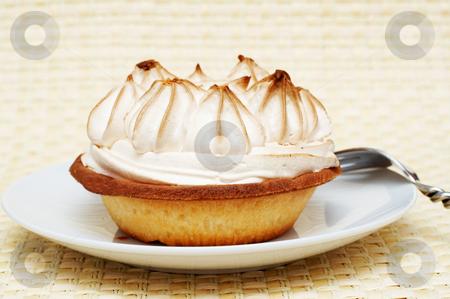 Miniature lemon meringue cake stock photo, Close-up of miniature lemon meringue cake with silver fork shot on a light wooden background by Elena Weber (nee Talberg)