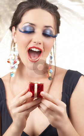 Portrait of beautiful brunette woman stock photo, Portrait of a beautiful young brunette woman with dramatic glamour make-up and fashionable earrings holding a little giftbox looking surprised on golden background by Elena Weber (nee Talberg)