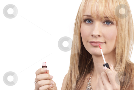 Portrait of beautiful blonde woman stock photo, Portrait of a beautiful blonde woman with light blue eyes applying pink lipgloss to her lips by Elena Weber (nee Talberg)