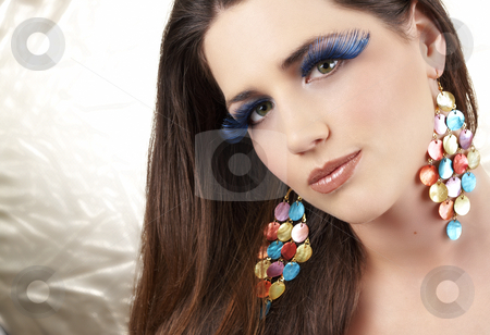 Portrait of beautiful brunette woman stock photo, Portrait of a beautiful young brunette woman with dramatic glamour make-up and fashionable earrings on golden background by Elena Weber (nee Talberg)