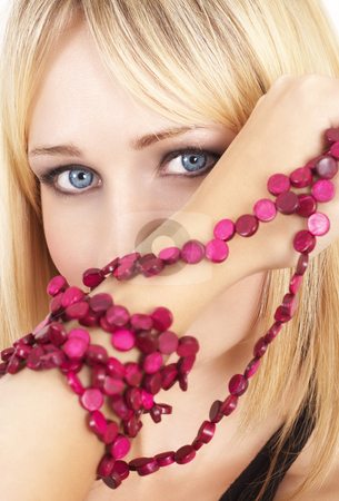 Portrait of beautiful blonde woman stock photo, Portrait of a beautiful blonde woman with light blue eyes and dramatic make-up holding pink beads next to her face by Elena Weber (nee Talberg)