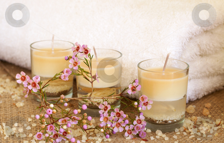 Relaxing spa scene with flowers stock photo, Relaxing spa scene with a white rolled up towel, small pink flowers, beautiful handmade candles and bath salts by Elena Weber (nee Talberg)