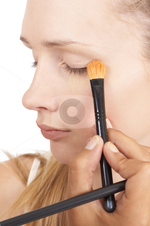 Portrait of beautiful blonde woman stock photo, Portrait of a beautiful blonde woman with natural make-up being applied by make-up artist isolated on white background by Elena Weber (nee Talberg)