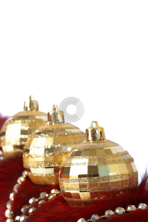 Golden Christmas baubles on fur stock photo, Three golden Christmas baubles with gold beads on red fur isolated on white background with copy space. Shallow depth of field by Elena Weber (nee Talberg)