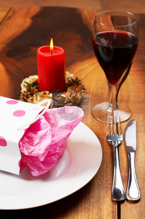 Table setting with a gift bag on plate stock photo, Table setting with a pink polka-dot gift bag on white plate and candle in the background by Elena Weber (nee Talberg)