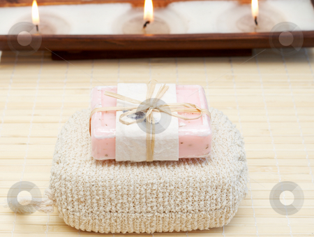 Relaxing spa scene with body products stock photo, Relaxing spa scene with body products - exfoliating sponge and handmade soap with candles in the background by Elena Weber (nee Talberg)