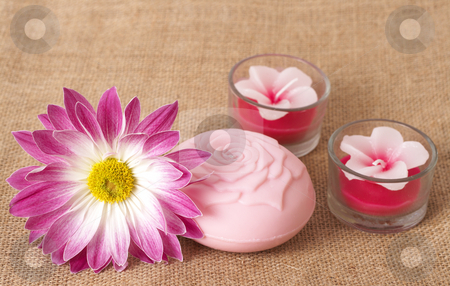 Relaxing spa scene with flower stock photo, Relaxing spa scene with a pink daisy flower, rose flavoured soap and beautiful handmade candles on brown mesh material by Elena Weber (nee Talberg)