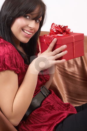 Portrait of beautiful brunette woman stock photo, Portrait of a beautiful young brunette woman sitting on a couch and holding a gift box at a celebration. Not isolated by Elena Weber (nee Talberg)