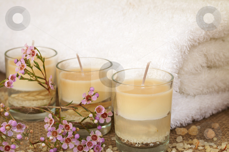 Relaxing spa scene stock photo, Relaxing spa scene with a white rolled up towel, pink flowers, beautiful handmade candles and bath salts by Elena Weber (nee Talberg)