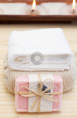 Relaxing spa scene with body products stock photo, Relaxing spa scene with pink handmade soap, sponge, white towel and candles in the background by Elena Weber (nee Talberg)