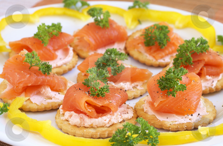 Smoked salmon and cream cheese on crackers stock photo, Smoked salmon and cream cheese on mini crackers with freshly cracked black pepper and garnishing of parsley by Elena Weber (nee Talberg)