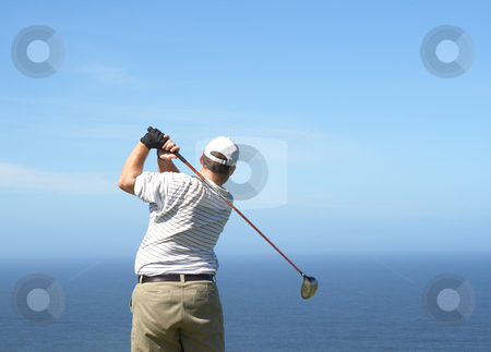 Golfer on the tee box stock photo, Young male golfer hitting the ball from the tee box next to the ocean on a beautiful summer day by Elena Weber (nee Talberg)