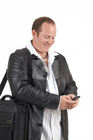 Businessman holding a cellphone stock photo, Young successful businessman wearing leather jacket smiling at a message on his cellphone. Isolated on white background by Elena Weber (nee Talberg)