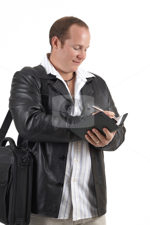Businessman holding a diary stock photo, Young successful businessman wearing leather jacket writing in his daybook and smiling. Isolated on white background by Elena Weber (nee Talberg)