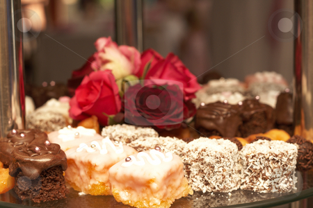 Selection of petit-fours stock photo, Selection of miniature petit-fours - coconut, chocolate cream and vanilla cakes on glass plate with roses by Elena Weber (nee Talberg)