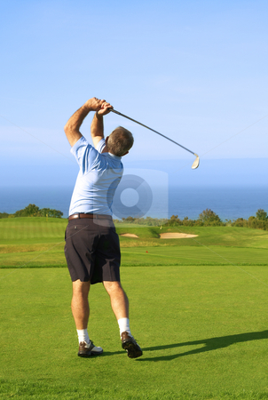Senior golfer playing golf stock photo, Senior male golfer playing golf from the tee box next to the ocean on a beautiful summer day by Elena Weber (nee Talberg)