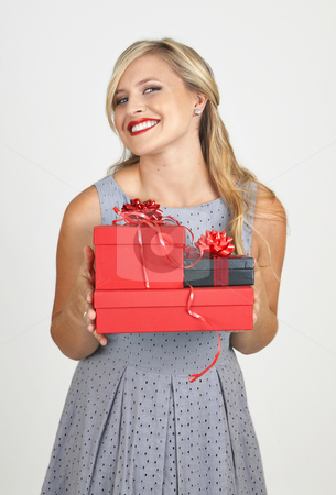 Portrait of beautiful blonde woman stock photo, Portrait of a beautiful blonde woman with light blue eyes and evening make-up holding gift boxes on grey background by Elena Weber (nee Talberg)