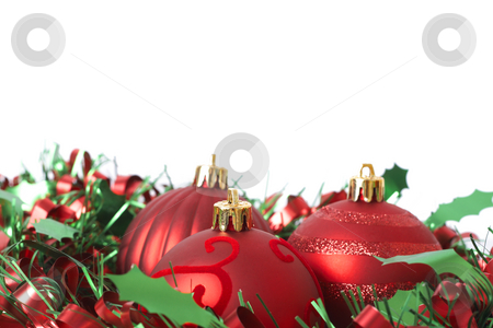 Three Red Christmas baubles on tinsel stock photo, Three red Christmas baubles on green and red tinsel isolated on white background with copy space. Shallow depth of field by Elena Weber (nee Talberg)