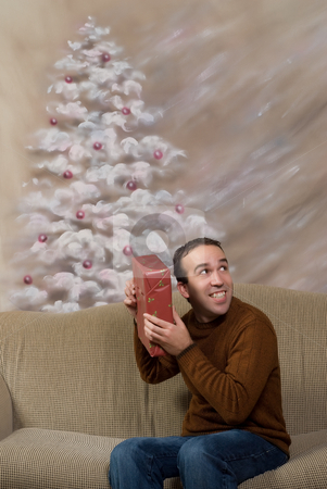 Guess The Present stock photo, A young man smiling and shaking his Christmas gift to guess what it is, shot in front of a hand painted background by Richard Nelson