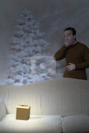 Glowing Xmas Gift stock photo, A christmas box is glowing at night in the living room, with a man covering his mouth in surprise by Richard Nelson