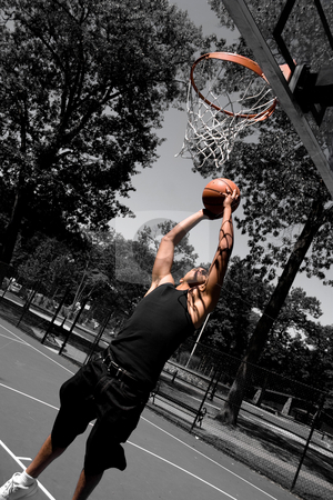 Player Dunking stock photo, A young man driving to the basketball hoop for a dunk with selective color. by Todd Arena