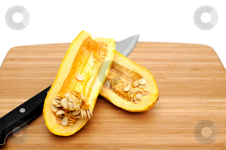 Delicata Squash stock photo, Delicata squash sliced in half exposing the many seeds inside on a bamboo cutting board by Lynn Bendickson