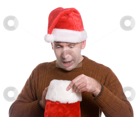 Stocking Stuffer stock photo, A young man wearing a Santa hat is looking inside his Christmas stocking and looks surpised, isolated against a white background by Richard Nelson