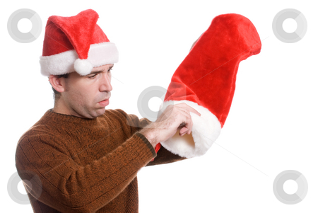 Empty Xmas Sock stock photo, A young man wearing a Santa hat is dumping out his Xmas sock, isolated against a white background by Richard Nelson