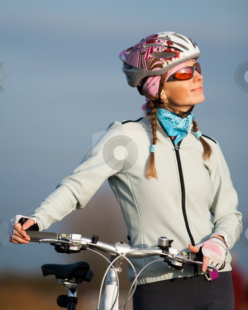 Active young woman with her bicycle stock photo, Active young woman with her bicycle. Smiling and looking at the sun by Peter Kirillov