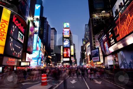 Times Square by Night stock photo, Night scene of Times Square in Manhattan (New York City) with all the lit up billboards and advertisements, and many tourists people walking by. by Paul Hakimata