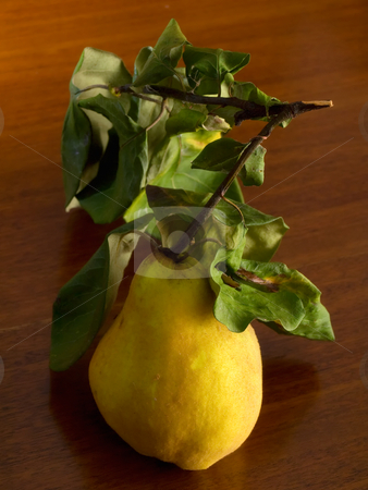 Quince stock photo, Ripe yellow quince with leaves on a wooden background. by Sinisa Botas