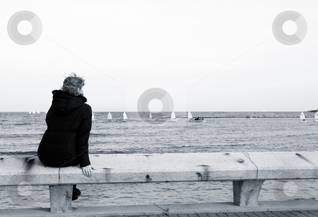Antibes #66 stock photo, Tourist sitting on a bench overlooking the sea in Antibes, France.  Blue tone.  Copy space. by Sean Nel