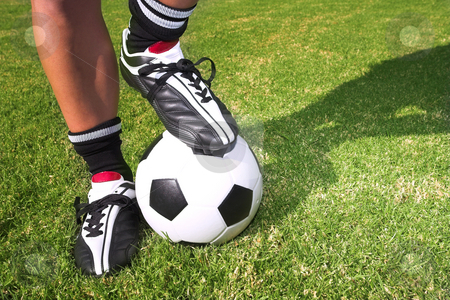 Football player with a soccer ball on soccer pitch stock photo, A male soccer (football) player, referee or coach standing with one foot on a soccer ball. The image is of feet and legs, with soccer togs, and a black and white ball by Sean Nel