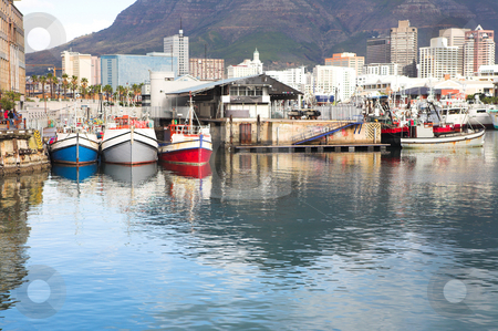 Cape Town Waterfront stock photo, Cape Town waterfront harbor with three boats reflecting in the water and the City skyline in the background. by Sean Nel