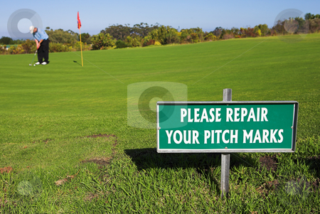 Gofer #40 stock photo, A golfer playing golf on a green.  Shallow D.O.F - sign in focus, golfer out of focus. by Sean Nel