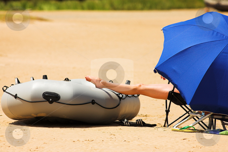Beach #1 stock photo, Woman relaxing on the beach under a blue umbrella by Sean Nel