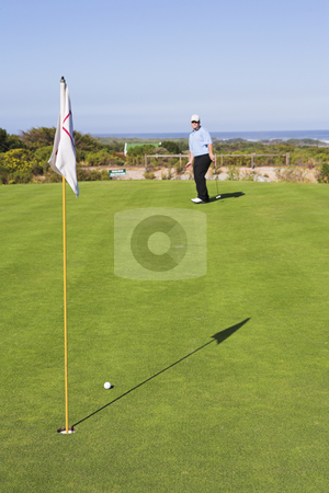 Golf #32 stock photo, Man playing golf, d.o.f. man out of focus, flag in focus. by Sean Nel
