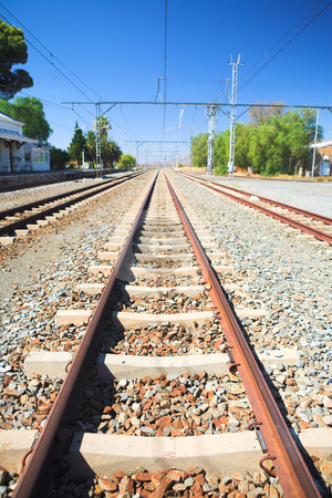 Train tracks and station stock photo, Train tracks in front of the train station of the desert town of Matjiesfontein in the Western Cape, South Africa by Sean Nel