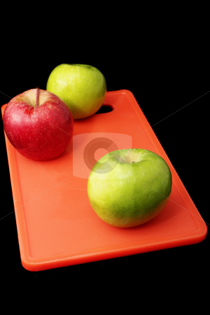 Apple #5 stock photo, Green and red apples on red plastic cutting board - black background by Sean Nel