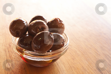 Bowl of olives stock photo, Small glass bowl of pitted black calamata olives in oil on a brown wooden table by Sean Nel