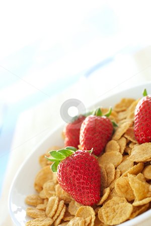 Breakfast cereal with strawberries and cream stock photo, Fresh red strawberries and breakfast cereal in a white bowl on a kitchen table by Sean Nel