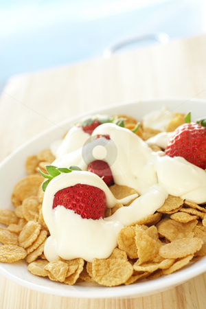 Breakfast cereal with strawberries and cream stock photo, Fresh red strawberries and thick dairy cream on breakfast cereal in a white bowl on a kitchen table by Sean Nel