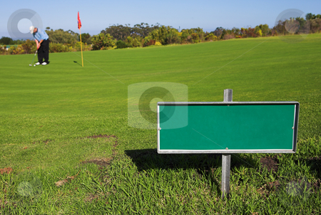 Gofer #41 stock photo, A golfer playing golf on a green.  Shallow D.O.F - sign in focus, golfer out of focus. by Sean Nel