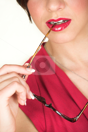 Young caucasian businesswoman stock photo, Young adult brunette businesswoman biting her horn rimmed glasses and a red dress. She is Caucasian and wears bright red lipstick. White background, not Isolated by Sean Nel