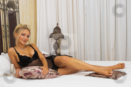 Linger #3 stock photo, Girl lying on bed wearing black lace lingerie by Sean Nel