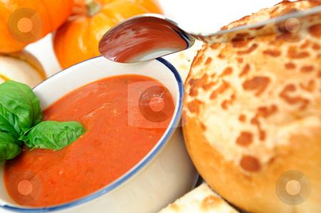 Tomato Soup And Basil stock photo, Hot tomato soup on an autumn day topped with fresh basil leaves and a French bread roll on the side by Lynn Bendickson