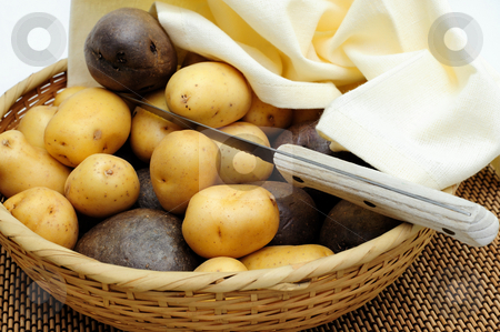 New Potatoes stock photo, Small yellow and purple new potatoes in a wicker basket and small paring knife by Lynn Bendickson
