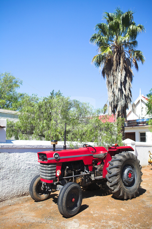 Old red tractor stock photo, Old red tractor standing on a farm yard on a sunny day by Sean Nel